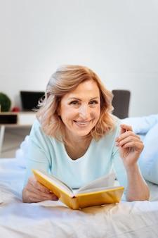 Bladeren door pagina's. vrolijke lichtharige vrouw die op haar bed rust en een interessant boek leest terwijl ze alleen thuis is