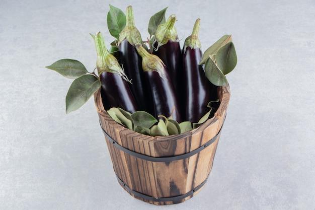 Bladeren en aubergines in de emmer, op het marmeren oppervlak