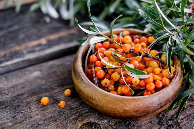 Bladeren en bessen van oranje duindoorn op houten lijst