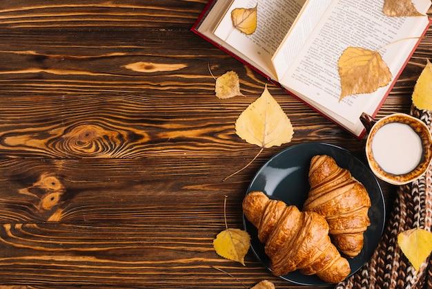 Bladeren en boeken in de buurt van croissants en drinken