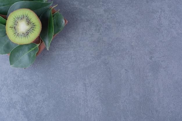 Bladeren en kiwi op houten plaat op marmeren tafel.