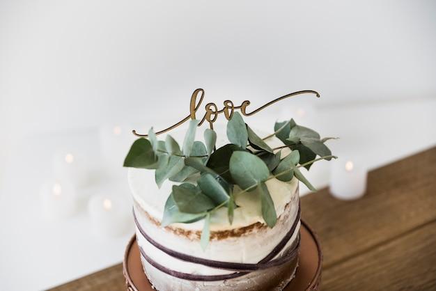 Bladeren en liefdetekst op decoratieve ronde cake over de houten lijst