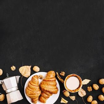 Bladeren en noten dichtbij drank en gebakje