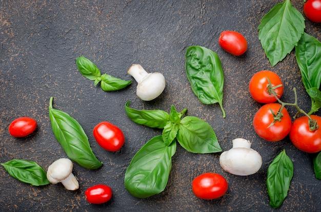Bladeren groene basilicum, cherry tomaten, champignon en peper kruiden