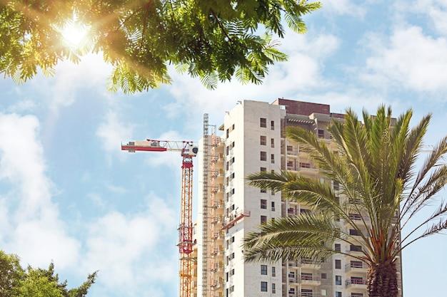 Bladeren van een palmboom op een achtergrond van hoge torenkraan en residentiële flatgebouwen in aanbouw tegen blauwe hemel. vastgoed ontwikkeling. nieuwe haus in framing stage