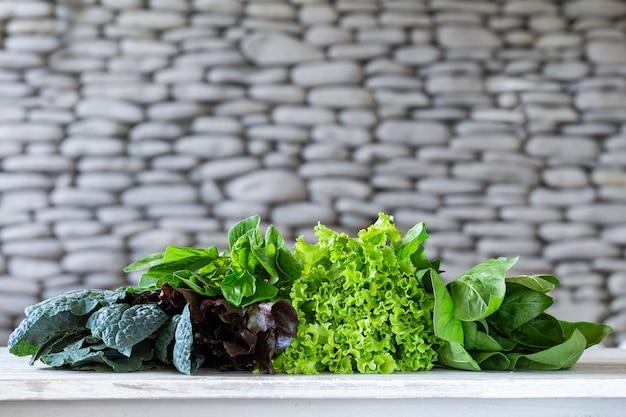 Bladeren van groene en rode sla, boerenkool, amarant op witte lijst met steen