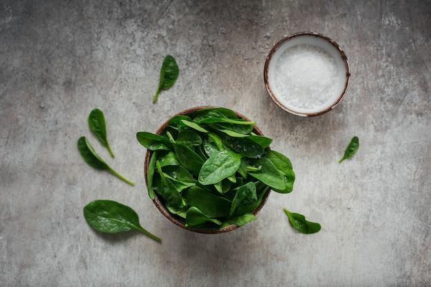 Bladeren van verse babyspinazie in een kom. bovenaanzicht van donkere biologische groene bladeren en zout. gezond veganistisch voedsel lifestyle concept. bovenaanzicht
