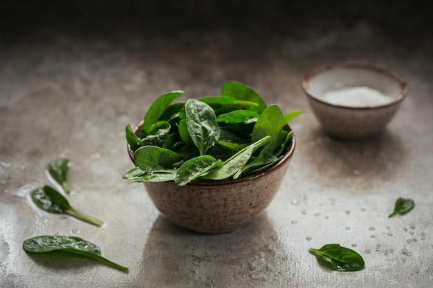 Bladeren van verse babyspinazie in een kom. donkere biologische groene bladeren en zout. gezond veganistisch voedsel lifestyle concept