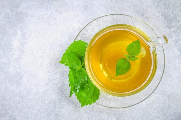 Bladeren van verse groene netel en een helder glas kopje kruidenthee op een grijze betonnen tafel.