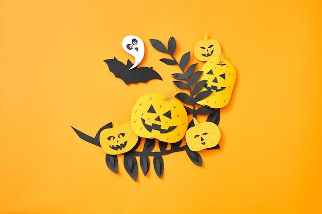 Bladeren, vliegende vleermuis, spook en pompoen met een eng gezicht op een oranje achtergrond met ruimte voor tekst. hand ambachtelijke papier samenstelling naar halloween. plat leggen