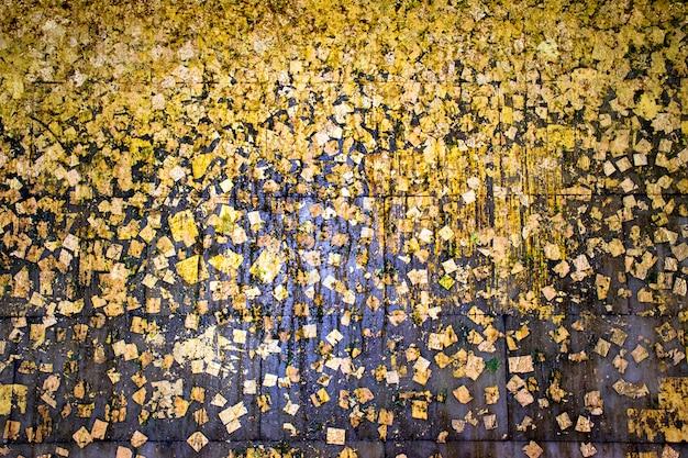 Bladgoud of gouden folie op zwarte textuur als achtergrond