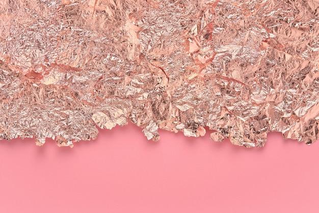 Bladgoudrand, gescheurde folieranden op roze, abstracte achtergrond.