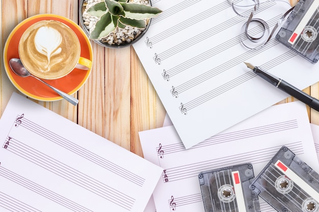 Bladmuziek cactus vulpen tape cassette en koffie latte op houten tafel