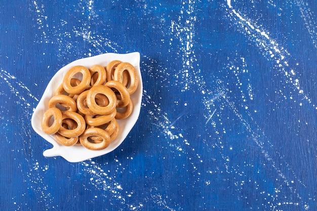 Bladvormige plaat van gezouten ronde pretzels geplaatst op kleurrijke plaat
