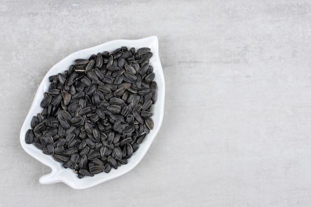 Bladvormige plaat vol met zwarte zonnebloempitten op steen.