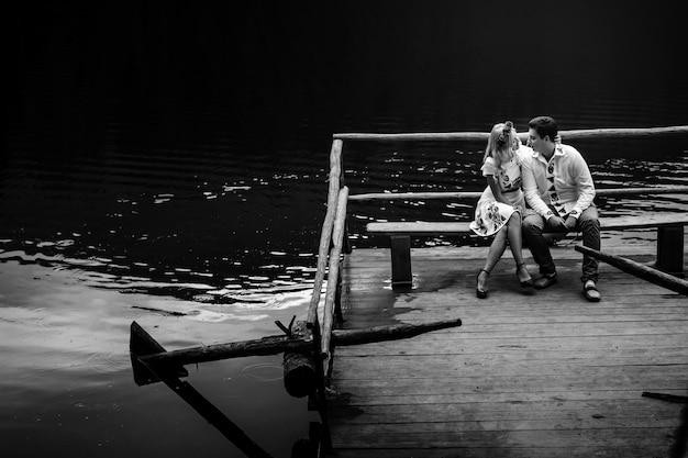 Blakc en witte foto van jonge mensen die op de bank over het meer kussen
