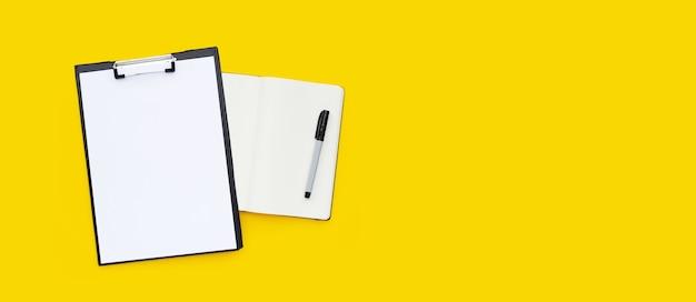 Blanco a4-papier in zwart klembord met notitieboekje en pen op gele achtergrond.