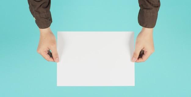 Blanco a4-papier. leeg wit bord in de hand van de man en draag marine shirt op groene munt of tiffany blue achtergrond.