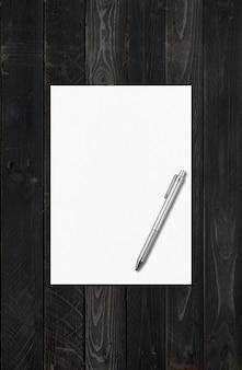 Blanco a4-vel papier en pen sjabloon geïsoleerd op zwarte houten achtergrond