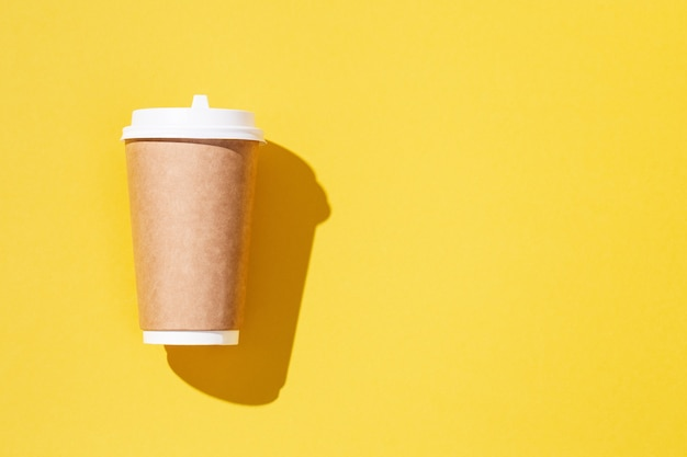 Blanco ambacht neemt grote papieren beker mee voor koffie of drankverpakkingen op geel gekleurde achtergrond