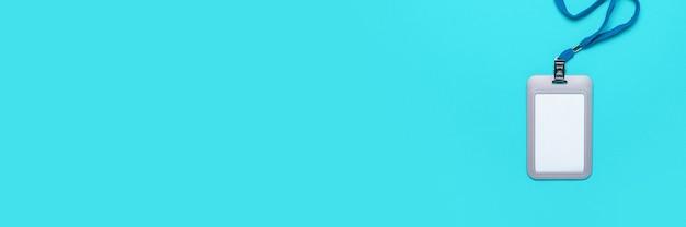 Blanco badge met koord op een lichtblauw oppervlak