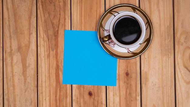 Blanco blauw papier voor citaten met koffie op de bovenste houten tafel