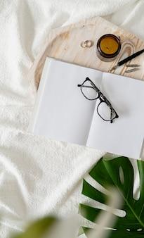 Blanco boek en kaarsen over houten dienblad, glazen, bloemen en palmblad over een wit bed, plat gelegd
