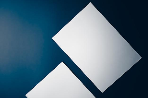 Blanco een papier wit op blauwe achtergrond als kantoorbenodigdheden flatlay luxe branding plat lag en merkidentiteitsontwerp voor mockup