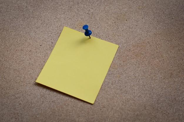 Blanco geel papier notitie vastgemaakt aan kurk boord met witte thumbtacks, kopie ruimte beschikbaar