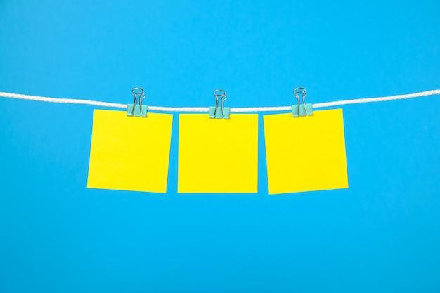 Blanco geel papier notities op waslijn