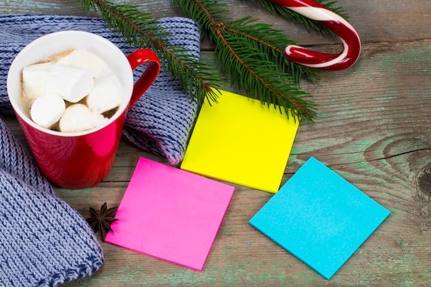 Blanco gekleurde plaknotities klaar voor bericht en kopje koffie met decoratie op houten bord.