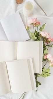 Blanco geopende boeken en bloemen op wit bed, plat gelegd