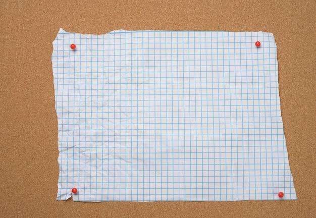 Blanco gescheurd verfrommeld wit vierkant vel papier vastgemaakt aan bruin kurkbord