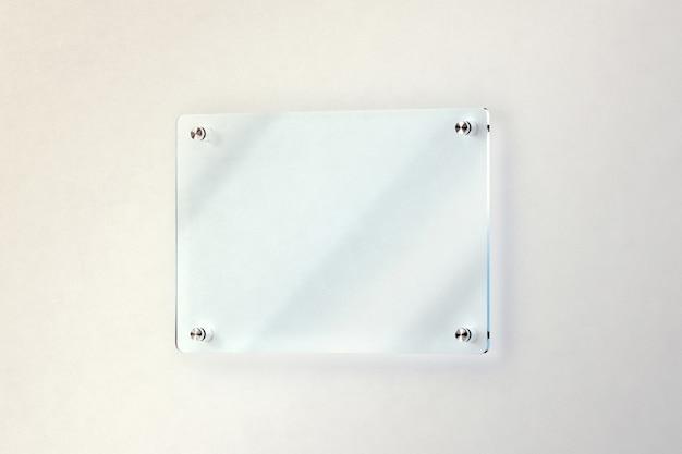 Blanco glazen deurplaat gemonteerd op de muur