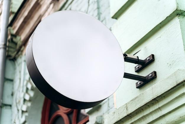 Blanco huisnaambordje. lege witte ruimte voor nummer, tekst of winkelnaam op de bakstenen muur. minimalistisch ontwerp voor reclameconcept