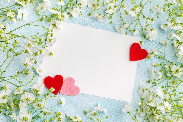 Blanco kaart en drie kleine harten tussen gypsophial bloemen