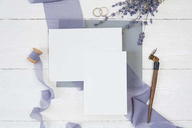 Blanco kaart en lint met twee trouwringen met lavendelbloemen