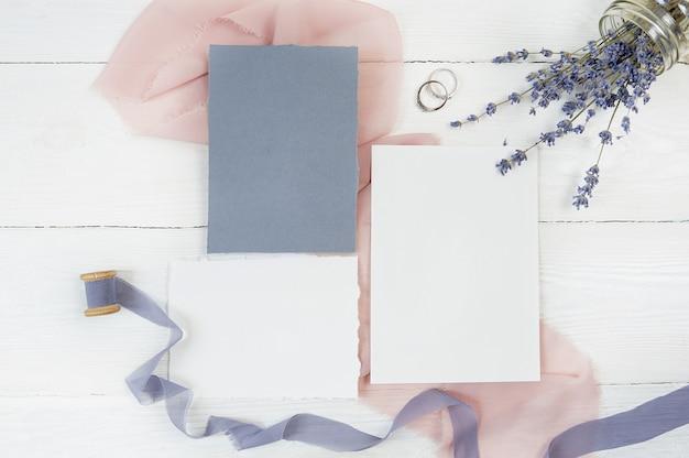 Blanco kaart en lint met twee trouwringen op een achtergrond van roze stof met lavendel bloemen