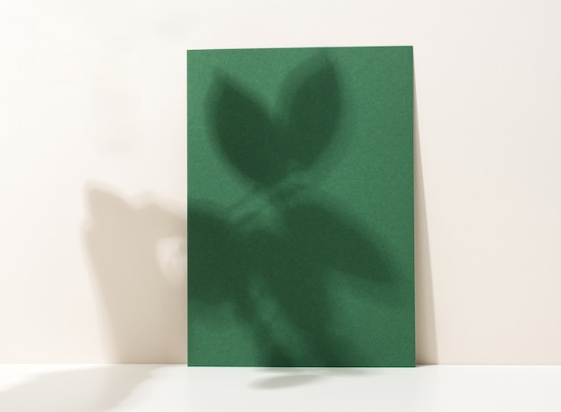 Blanco kartonnen vel papier met schaduw op witte tafel. sjabloon voor flyer, aankondiging
