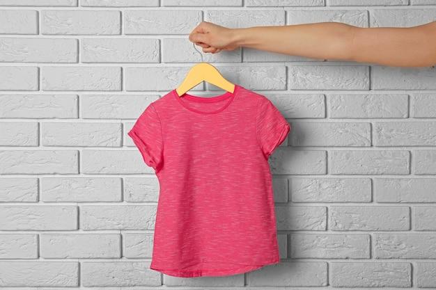 Blanco kleurent-shirt tegen bakstenen muur