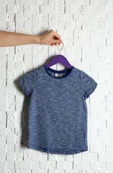 Blanco kleurent-shirt tegen licht getextureerde muur