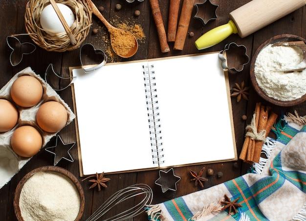 Blanco kookboek, ingrediënten en keukengerei bovenaanzicht