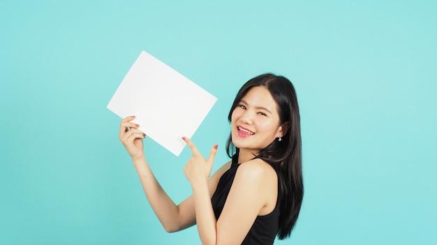 Blanco leeg papier in de hand van de aziatische vrouw en wijzende vinger op mintgroen of tiffany blue achtergrond.