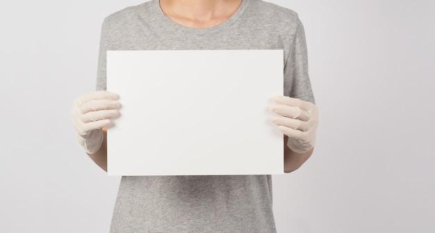 Blanco leeg papier in de hand van de vrouw en draag medische handschoen op witte achtergrond.