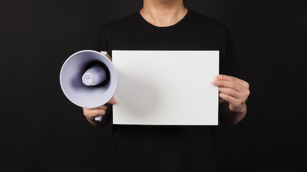 Blanco leeg papier in iemands hand met megafoon op zwarte achtergrond.