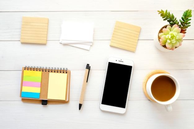 Blanco notitieblaadjes, visitekaartje, slimme telefoon, pen en koffie op wit