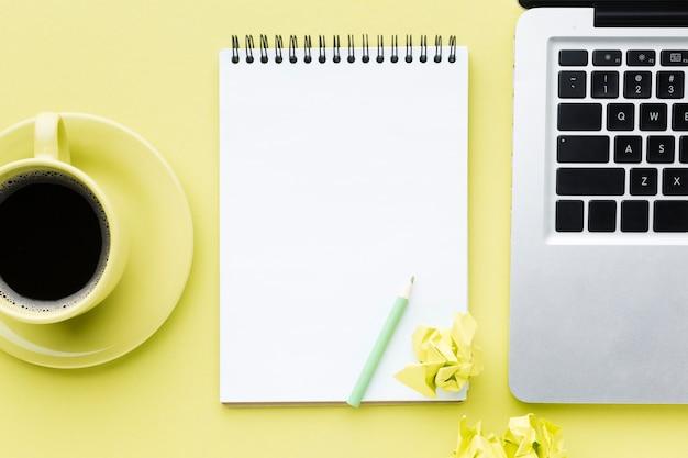 Blanco notitieblok en laptop bovenaanzicht