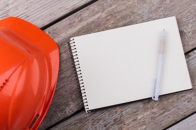 Blanco notitieblok met pen en bouwhelm. oude vintage houten tafel op de achtergrond.
