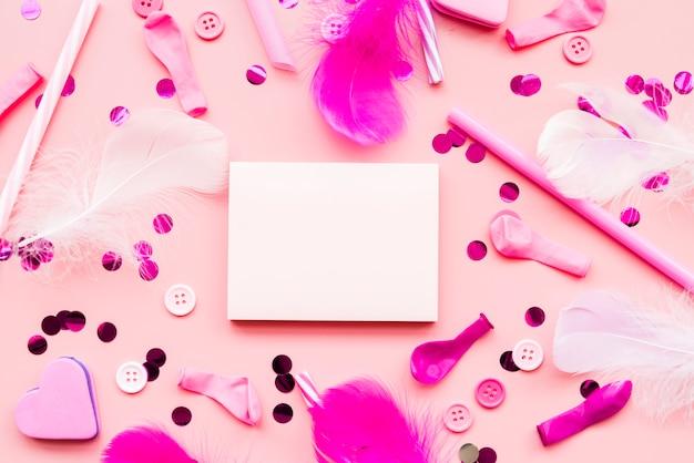 Blanco notitieblok omringd met pailletten; toetsen; veer; ballon; rietje op roze achtergrond