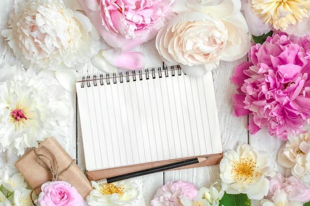 Blanco notitieboek in bloemenlijst van roze en witte pioen, rozen en jasmijnbloemen en geschenkdoos